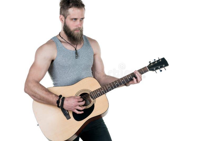 Charyzmatyczny mężczyzna z brodą trzyma gitarę akustyczną na białym odosobnionym tle, Horyzontalna rama fotografia stock