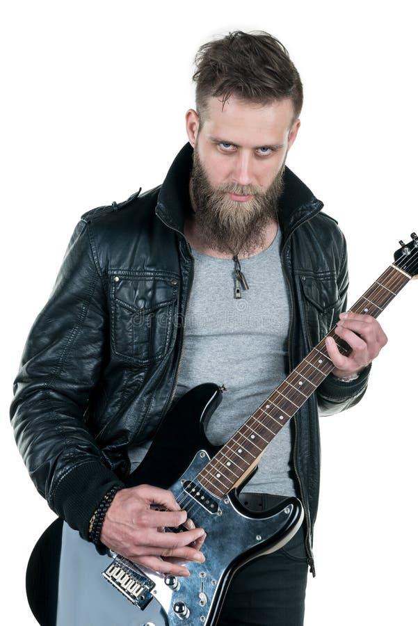 Charyzmatyczny mężczyzna z brodą w skórzanej kurtce, bawić się gitarę elektryczną na białym odosobnionym tle, Horyzontalna rama fotografia royalty free