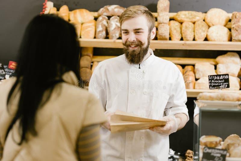 Charyzmatyczny piekarz z w?sy i brod? daje papierowej torbie chleb klient w piekarni fotografia stock