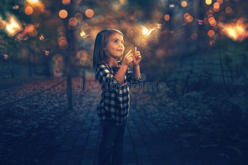 Chasing butterflies. A little girl chasing glowing butterflies at night stock image
