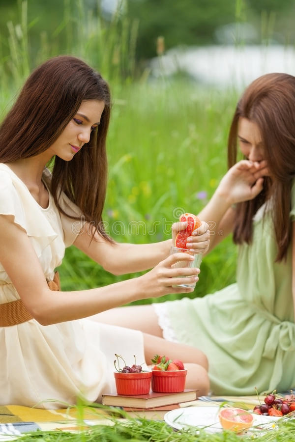 Chasing wellness. Two girl are having fun on picnic squeezing grapefruit while chasing healthy lifestyle stock photo