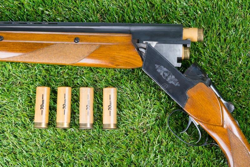 Chasse du fusil à côté de trois balles sur une pelouse verte photo libre de droits