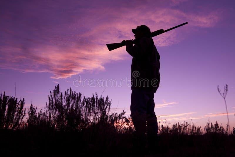 Chasseur avec le fusil de chasse dans le coucher du soleil image libre de droits