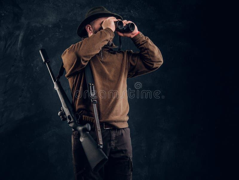 Chasseur avec le fusil de chasse observant par des jumelles Photo de studio sur le fond fonc? de mur image libre de droits