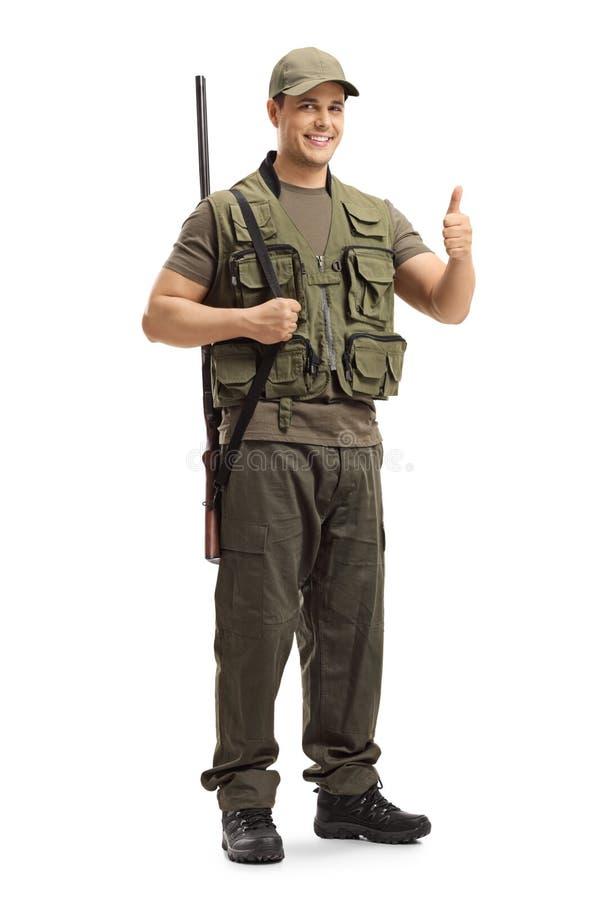 Chasseur avec un fusil de chasse sur son ?paule montrant des pouces vers le haut de signe photo stock