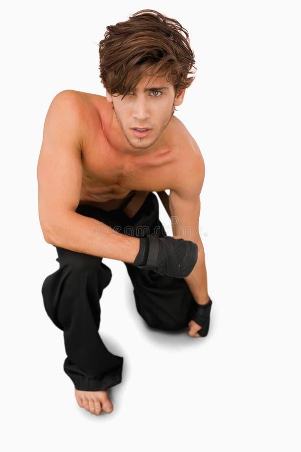 Chasseur d'arts martiaux sur ses genoux images libres de droits