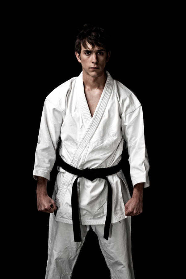 Chasseur mâle de karaté contrasté sur le noir photographie stock libre de droits