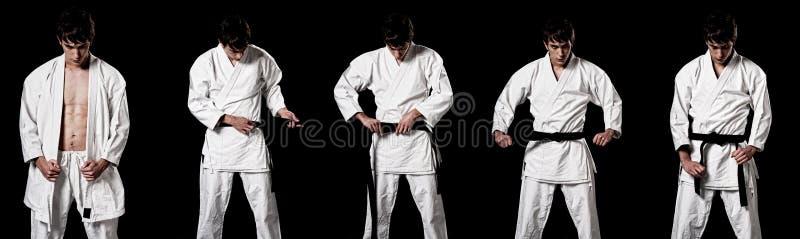 Chasseur mâle de karaté rectifiant le kimono contrasté photo libre de droits