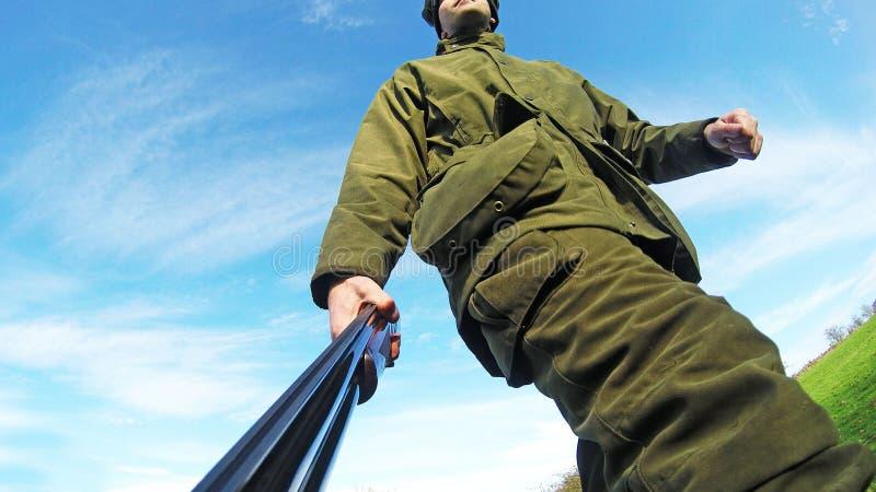 Chasseur marchant avec le fusil de chasse à une pousse photographie stock