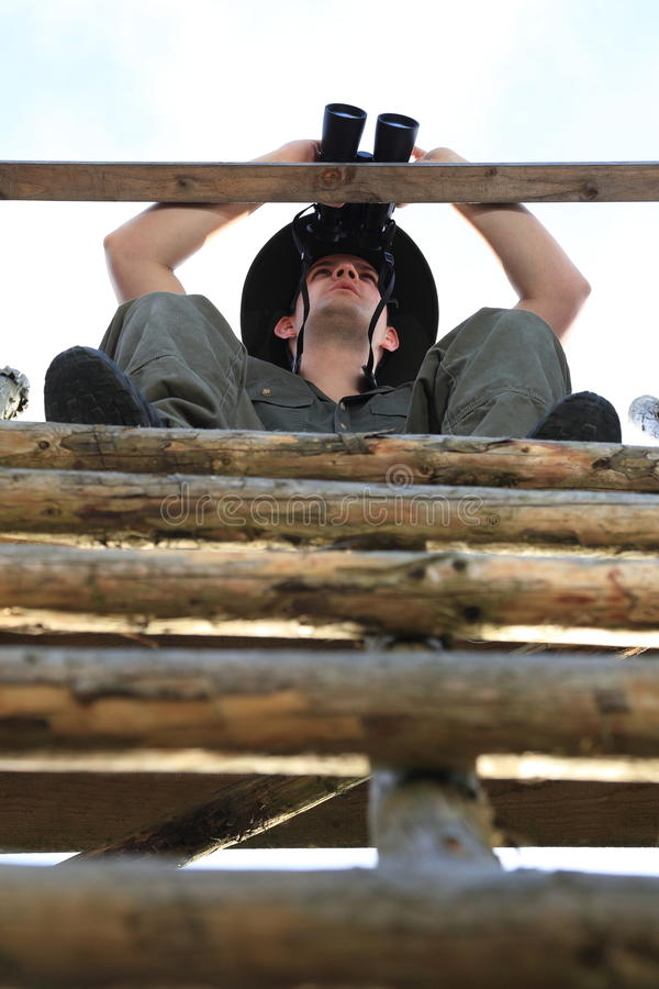 Chasseur observant avec des jumelles d'un siège élevé photo stock