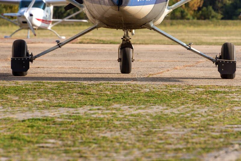 Chassi av sportflygplan och gräs arkivbild