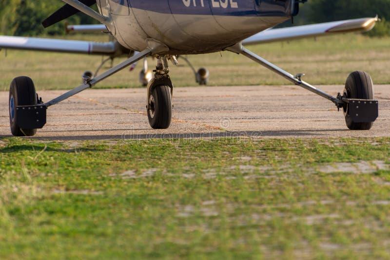 Chassi av sportflygplan och grönt gräs royaltyfri foto