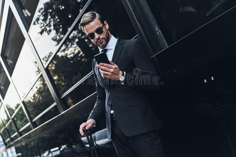Chat with client. Good looking young man in full suit using his smart phone while standing outdoors royalty free stock photos