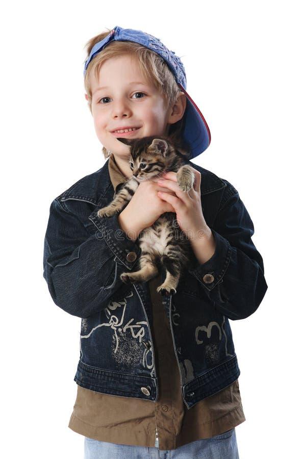 Chat de caresse d'animal familier de jeune garçon photographie stock