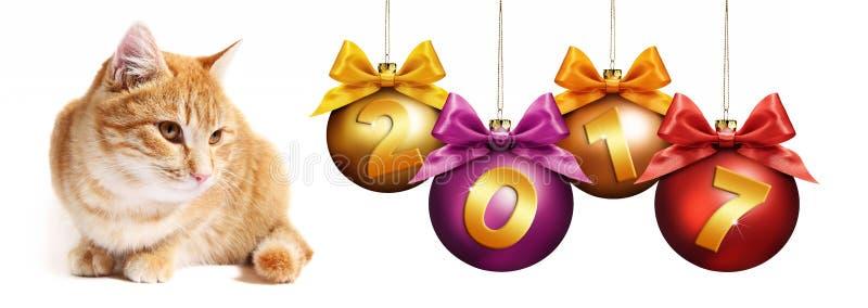 chat de gingembre des 2017 textes avec des boules de Noël avec l'arc de ruban photographie stock