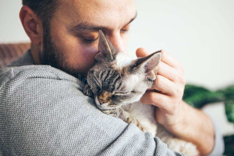 Chat et homme, portrait de chat heureux avec les yeux étroits et jeune homme de barbe photos stock