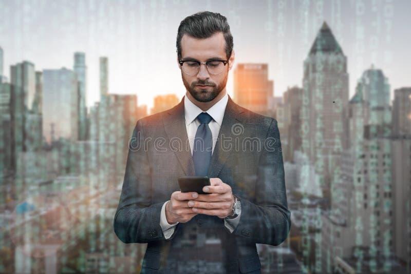 Chat mit Kunden Hübscher junger Geschäftsmann in der Klage unter Verwendung des Smartphone bei der Stellung gegen Stadtbildhinter lizenzfreie stockfotos
