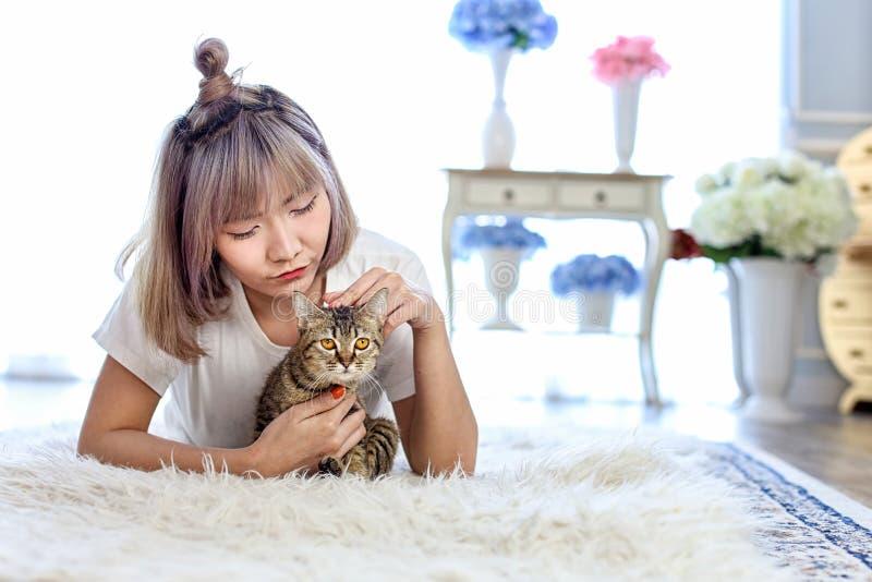 Chat thaïlandais dans l'étreinte de la femme se trouvant sur le tapis de laine r Beau images stock