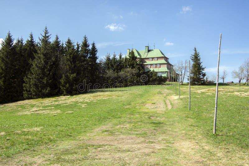 Chata de Masarykova, cottage en bois en montagnes sur la colline, printemps, herbe verte et ciel bleu images libres de droits