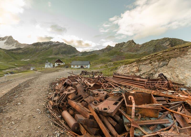 Chatarra de una vieja minería en las montañas, las casas e iglesia en el middleground Montañas en el fondo imágenes de archivo libres de regalías