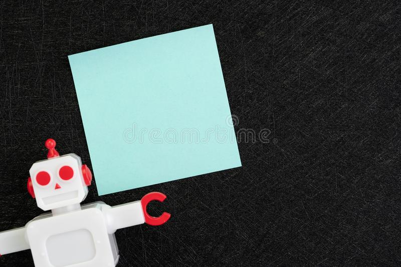 Chatbot, AI Artificial Intelligence concept, blue blank sticky note with vintage robot on dark black background with copy space to stock images