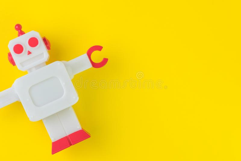 Chatbot or AI Artificial Intelligence or robotic concept, cute vintage look plastic robot on vivid yellow background royalty free stock image