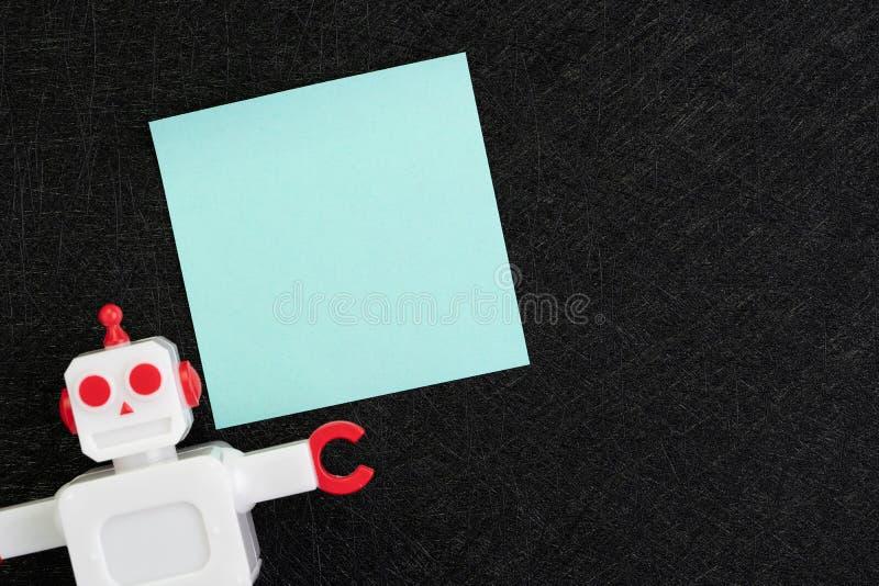 Chatbot, concept d'intelligence artificielle d'AI, note collante vide bleue avec le robot de cru sur le fond noir foncé avec l'es images stock
