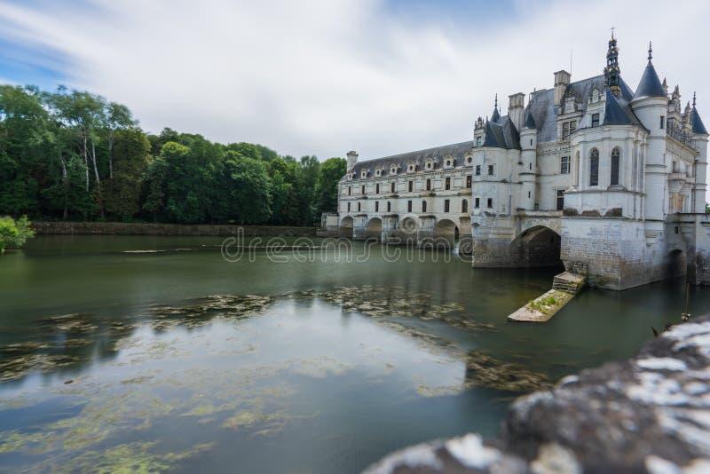 Chateau de Chenonceau med blå himmel & den silkeslena floden arkivbilder