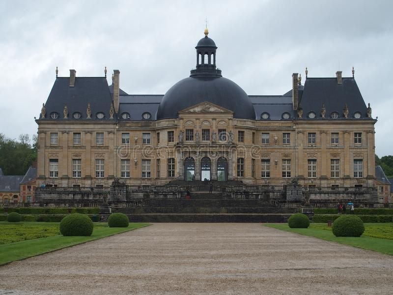 CHATEAU de VAUX le VICOMTE, front of largest private French castle at baroque style. And path in garden in town of MAINCY in FRANCE with cloudy sky in 2015 warm stock image