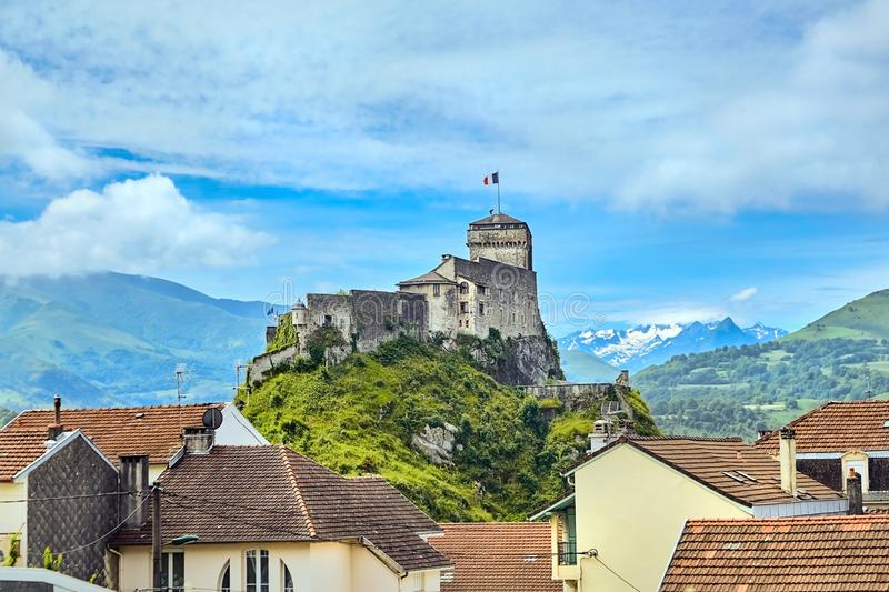 Chateau Fort of Lourdes. Castle on a rock. Snowy mountain peaks. Blue sky with white clouds. Town in the Hautes-Pyrénées, France stock image
