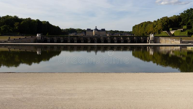 Chateau at Vaux-le-Vicomte reflected in a pond. The Chateau at Vaux-le-Vicomte is reflected in a pond in the surrounding garden royalty free stock photo