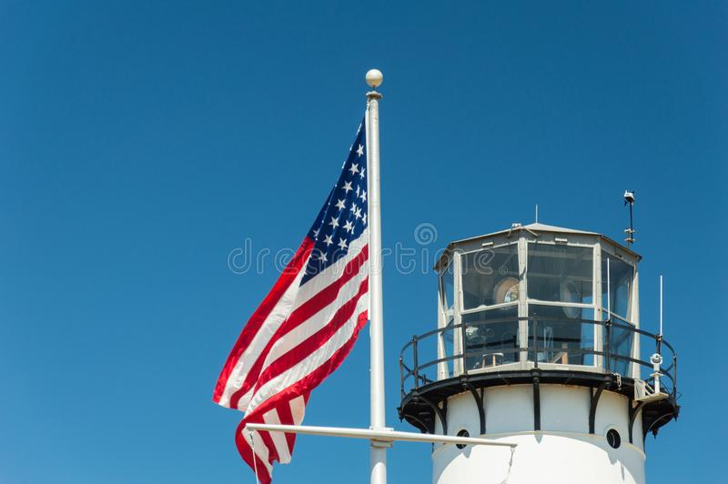 Lighthouse and US Flag. Chatham Light, a lighthouse in Chatham, Massachusetts, near the elbow of Cape Cod royalty free stock photo