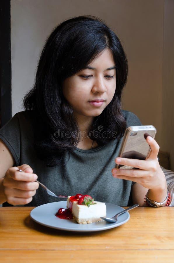 Chating Handy der jungen asiatischen Frau mit einem Kuchen lizenzfreie stockfotos