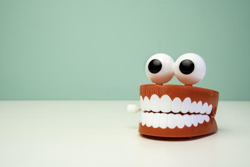 Chattering teeth toy on a table with a green background royalty free stock photo
