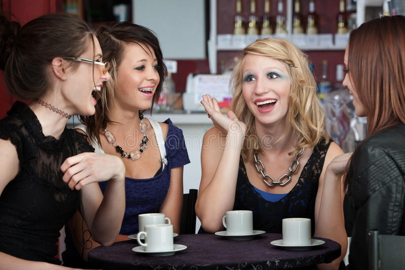 Chatting in a Coffee Shop. Four college freshmen chatting in a coffee shop royalty free stock photography
