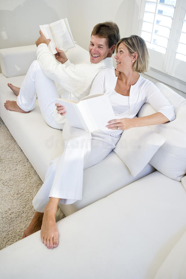 chatting couple reading sofa together στοκ φωτογραφίες