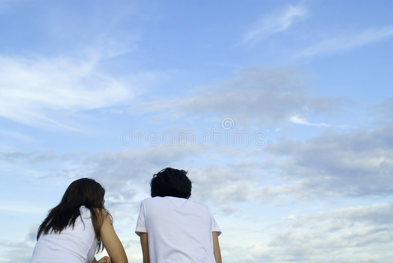 Chatting couple with sky. A guy and girl chatting with a beautiful sky royalty free stock images