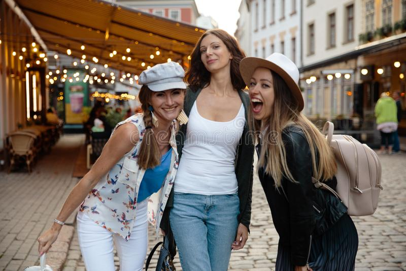 Chatting and laughing Three traveling girl friends with light backpacks exploring Riga city - Travel tourism concept royalty free stock photography