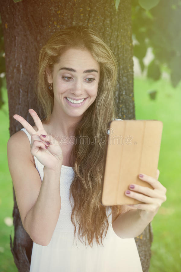 Chatting under the tree. Young charming woman charming under the tree via table pc royalty free stock image