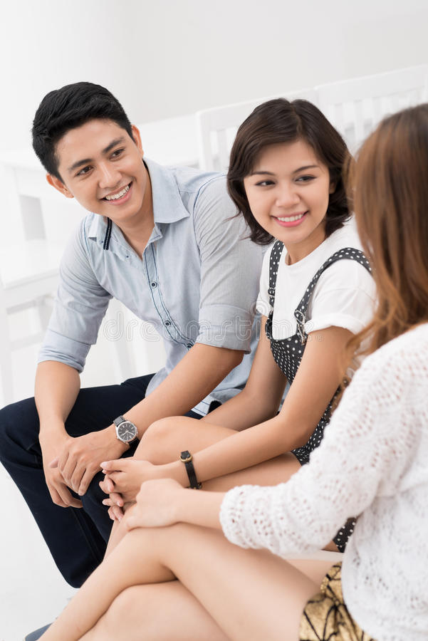 Chatting. Vietnamese young people chatting indoors royalty free stock images