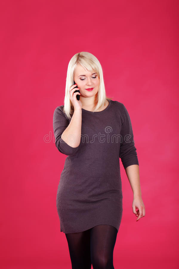 Chatty blonde. Girl talking on the phone on pink background stock photography
