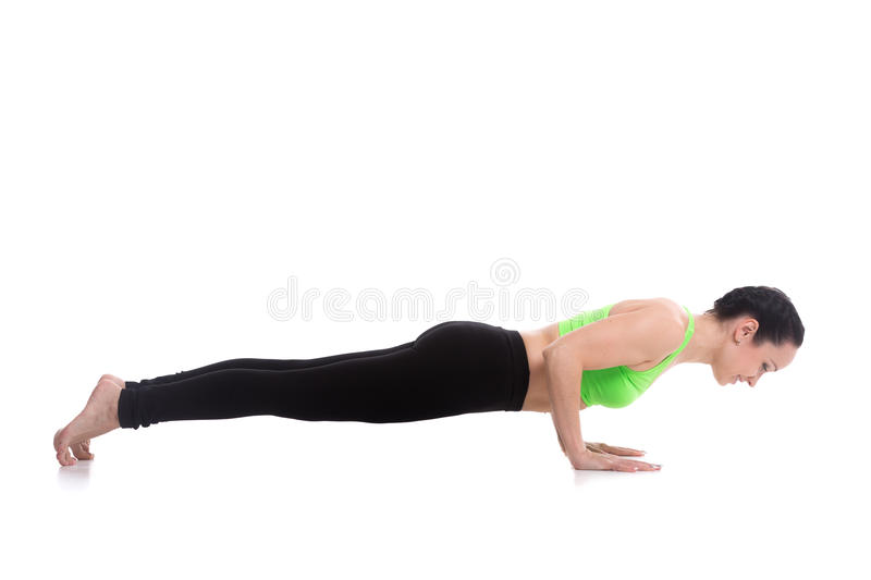 Chaturanga dandasana, four-limbed staff yoga pose. Sporty girl doing exercises for shoulders on white background, push-ups, chaturanga dandasana (four-limbed royalty free stock photos