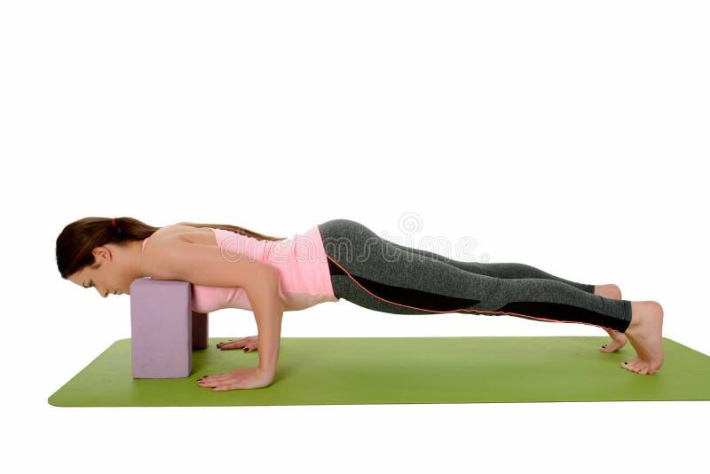 """Chaturanga Dandasana - la variación Cuatro-Limbed de la actitud del personal con yoga apoya correa o bloque del †"""" fotos de archivo libres de regalías"""