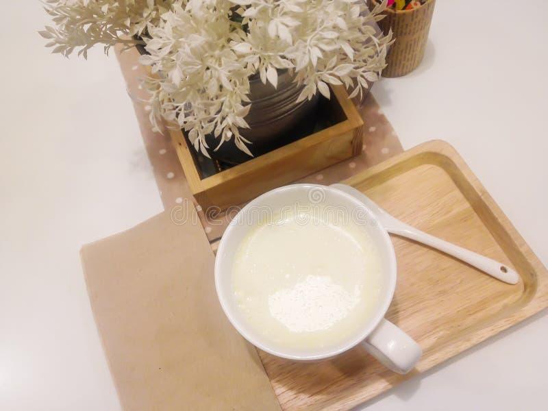 Chaud le lait dans une tasse blanche sur la table dans le blanc et décorée d'un arbre blanc photographie stock libre de droits