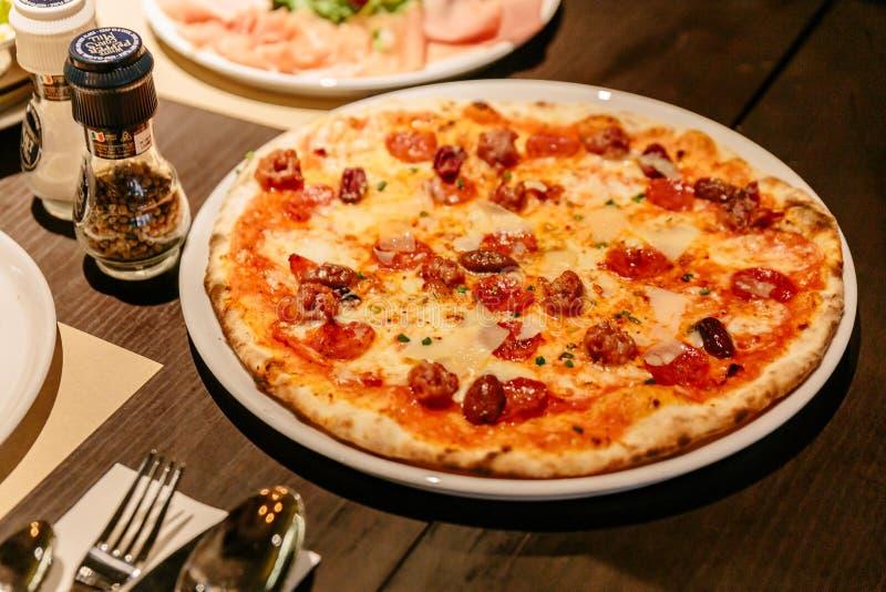 Chaud a servi la pizza Carbonara sur la table Les ingrédients sont base de tomate, mozzarella, oeuf, parmesan, lard et lard crous image libre de droits