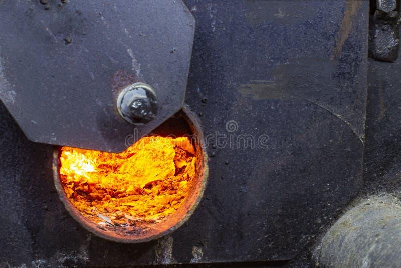 Chaudière à eau chaude avec l'intérieur de porte ouverte et de feu et scoop avec du charbon photo libre de droits