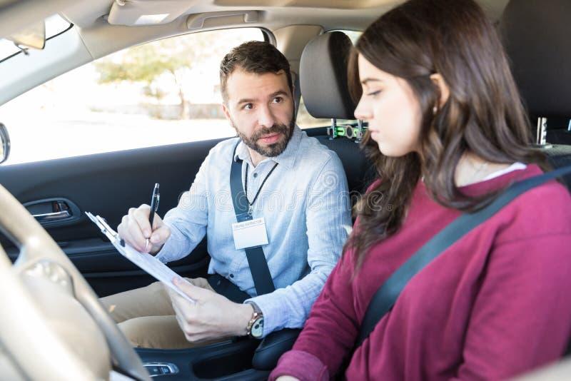 Chaufför för instruktörExplaining Checklist To ny bil royaltyfria foton