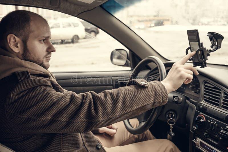 Chaufför för ung man som använder smartphonen i bil arkivfoto
