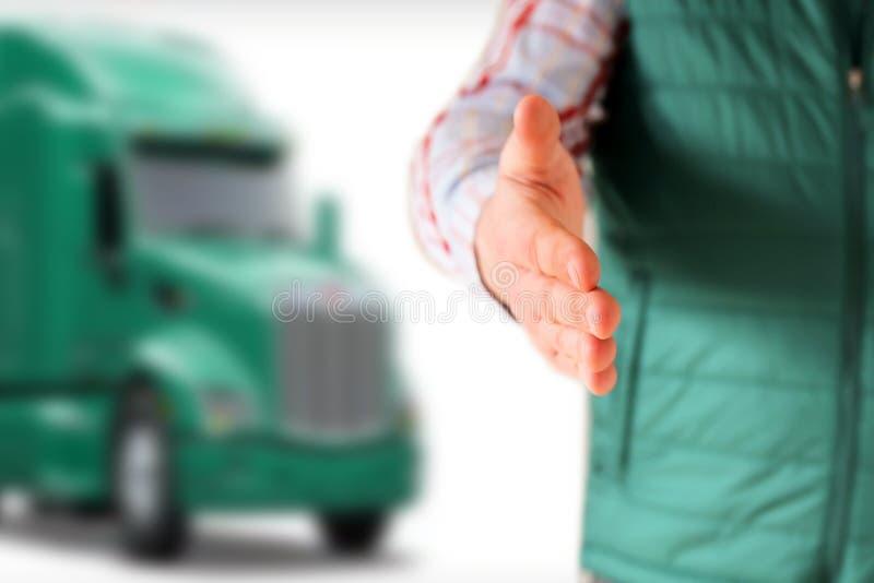 Chaufför med en öppen handhälsning Grön lastbil bak honom fotografering för bildbyråer