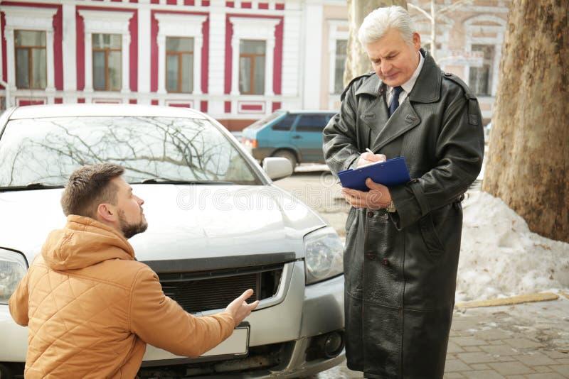 Chaufför som förklarar detaljer av olyckan till förlustregulatorn royaltyfri bild